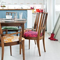 With compact cabinets and a kitchen island, this small coastal kitchen has enough room for a breakfast area. Varying vintage-inspired fabrics spice up simple dining chairs and bring color into this white kitchen area. (Photo: Thomas J. Fabric Dining Room Chairs, Woven Dining Chairs, Mismatched Dining Chairs, Kitchen Chairs, Table And Chairs, Dining Area, Chair Fabric, Eclectic Dining Chairs, Chair Pads