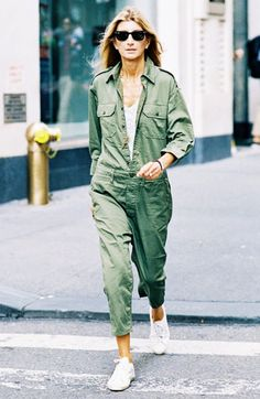 A v-neck t-shirt is layered underneath an army green jumpsuit, and paired with Ray-Ban sunglasses and white sneakers