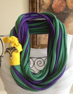 The Mardi Gras recycled/upcycled infinity t shirt/jersey scarf/necklace can be worn long or looped for a shorter chunkier version. This scarf is made from three recycled t-shirts and a fleur de lis type brooch, which can be removed if you fancy. Play with the loops to get the look you desire.  Dress it up with a light sweater or jacket and hit the town! $35.00. http://www.etsy.com/listing/94368274/long-recycledupcycled-t-shirtjersey?ref=v1_other_1
