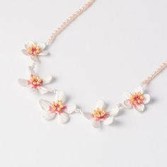 Almond Blossom Flowers Necklace by Michael Michaud is cast in bronze and features a matte silver finish with hand painted accents and yellow rice pearls. Strung on peach freshwater pearls.