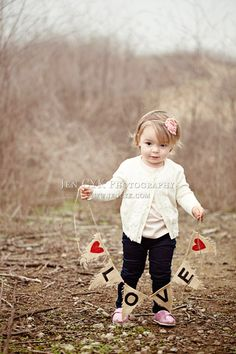 Ugly winter background but you don't notice. Toddler poses with props (my most favorite love banner). JEN CYK PHOTOGRAPHY