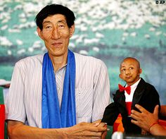 These pictures show a meeting between Bao Xishun and He Pingping. At 7 foot and 9 inches, Xishun is believed to be the world's tallest living man while Pingping, at 2 feet and 4 inches, is believed to be the world's smallest living person.