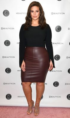 Ashley Graham in a black long-sleeve top and leather pencil skirt