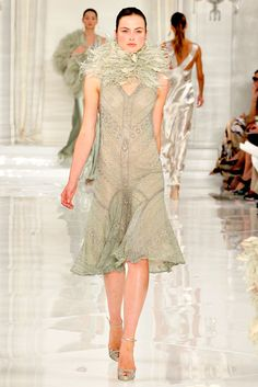 3/1/15 This Ralph Lauren dress is inspired by the 1920s because of the embellishments, dropped waist, and tubular silhouette. This dress is similar to that of the flapper dress of this time. The knee length and boa are key indicators of the 1920s, which is another measure of this time.