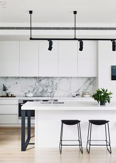 Black and white monochrome kitchen: handleless white cabinets and benchtops, grey marble splashback, black bar stools, black spotlights on suspended ceiling track, timber floorboards #WhiteKitchen