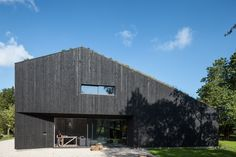Surrounded by traditional architecture, the Villa breaks the residential mold with a clean, modern form. The asymmetrical structure is clad entirely in blackened timber. Villa Design, Sustainable Architecture, Architecture Design, Villas, Modern Brick House, Looking For Houses, Contemporary Barn, Minimal Home, Tropical Houses