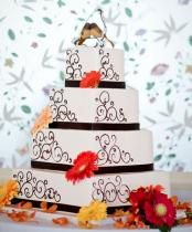 Four tier white square wedding cake with love bird toppers and fresh flowers and black bands.JPG