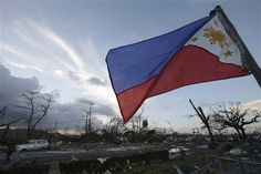 In this Saturday, Nov. 9, 2013 file photo, a Philippine flag stands amongst the damage caused after powerful Typhoon Haiyan slammed into Tacloban city, Leyte province, central Philippines. Haiyan slammed the island nation with a storm surge two stories high and some of the highest winds ever measured in a tropical cyclone. An untold number of homes were blown away, and thousands of people are feared dead. (AP Photo/Aaron Favila, File)