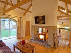 The Old Forge - Alnmouth Holiday Cottages - TripAdvisor - Before After DIY Wood Burner Fireplace, Brick Fireplace Makeover, Home Fireplace, Living Room With Fireplace, Fireplace Design, Double Sided Stove, Double Sided Fireplace, Open Plan Kitchen Living Room, Freestanding Fireplace