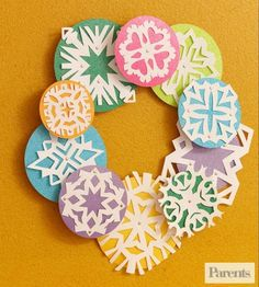 Paper snowflakes stand out when paired with pretty paper shapes. Glue them together in a circle, and you've got a door-worthy wreath.  Make It: Cut paper snowflakes out of white paper. Glue the snowflakes to colored construction paper circles. Then, attach all the circles together in the shape of a wreath.