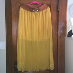 Mustard yellow colored maxi skirt w/belt Skirt is mustard colored with attached elastic belt. Skirt does have a few pulls in it. Skirts
