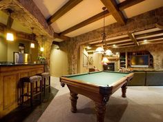 Not the flashiest man cave, but it does the job - mini-bar, billiards table and TV. Great stone walls and wood beam ceiling... yup that will do.