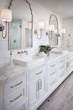 Calacatta marble countertop, white ship lap walls, pewter lamp sconces, white vanity with brushed nickel dainty hardware, and white-washed faux wood tile floors. Gorgeous white bathroom.