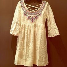 Adorable Embroidered Lace Dress Beige lace dress with Aztec embroidery. Made of cotton, nylon,& polyester. Tie in back. Short bell sleeve. Rounded back with crisscross detail. NWOT. Dresses Midi