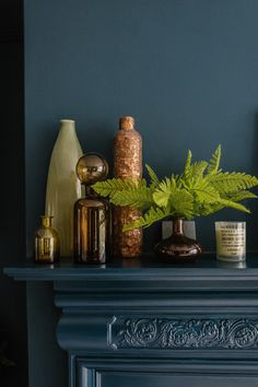 Dark green blue wall colour with vases and candles on a mantelpiece for modern eclectic style by Fiona Duke Interiors. With botanical greenery to add colour and copper toned accessories working well against the dark petrol blue paintwork.