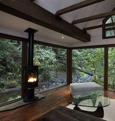 modern cabin with hanging fireplace and beautiful noguchi coffee table