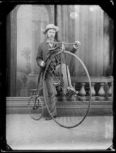 Studio portrait of an unidentified young man standing alongside a penny farthing bicycle. He wears a suit, a waistcoat, and a hat. He has sideburns and a moustache. Behind him is a low colonnade, a curtain, and a painted backdrop depicting columns and an urn. Photograph taken by William James Harding of Wanganui, circa 1880s.