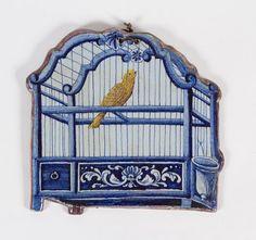 DELFT  Plaque d'applique chantournée en faïence polychrome.  Décor d'un oiseau perché dans une cage en camaïeu bleu.  Marque au dos.  XVIIIème siècle  (restaurations)  25 x 26 cm