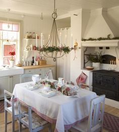 Vintage chic Christmas. Love the chandelier and the old stove and the white table cloth and table decor.