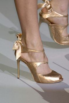 Zac Posen Spring 2007. These subtle peep-toe golden heels with bow detailing are super cute! They, paired with a little black dress, gold accessories and makeup, would look like a million dollars!