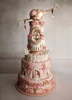 Exquisitely detailed wedding cake in pink, gold and white with a Rococo flair.  Loving the cherubs wrapping the heart topper and just about everything else!