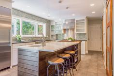 HGTV shows how a small, drab kitchen brightened up with the help of a 9' window over the sink, a trio of teardrop lights above the island and stark white cabinets surrounding the space.