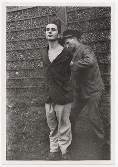 Carl Mydans - The second of six members of the Nazi collaborationist Milice, Vichy police, being tied to a post by a guard moments before being shot to death by a Maquis firing squad, in front of brick factory where twenty-three patriots were executed by the Germans in July, 1944.
