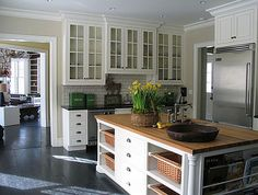 White cabinets, island with butcher block top, dark floors & counter tops, subway tile, cabinets to ceiling
