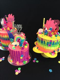 Trolls drip cakes, with fluoro rainbow icing and drips, chocolate poppy hair, lollipops, figurines of Poppy, Branch and troll friends and more! @edible_magic