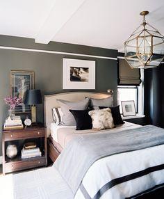 Oversized end table, dark walls, rug over hardwood, splash of color with vase