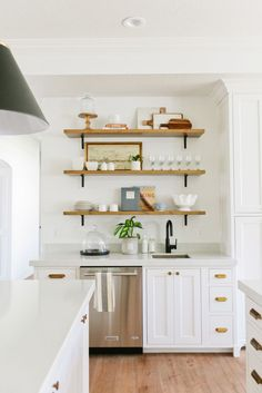 Gorgeous all-white kitchen with brass hardware, marble counters and wood open shelving.