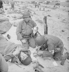 A US Medical Corpsman administers a saline drip to a fellow medic of 4th Infantry Division wounded on Uncle Red Beach, Utah area, 6 June 1944.
