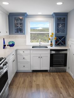 Beach house kitchen remodel by Renovisions with blue and white kitchen cabinets, wine storage, hardwood floors, Silestone countertops and stainless steel appliances.