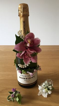 Wedding flowers corsage rings and decorated champagne bottle with pearls, orchids and ivy and hyacinth buds