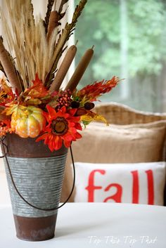 I love the rustic look of the tin and the color of the flowers and those cattails remind me of home!!