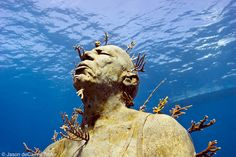 """Artist, Jason deCairs Taylor underwater sculpture -  """"Hombre en Llamas"""" (Man on fire) Isla Mujeres, Mexico.  The statues are made of a porous materials to encourage reef life to grow on and around them."""