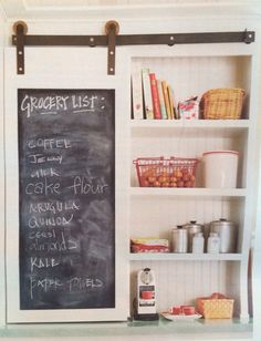 Love this sliding door on the front of the shelves instead of the standard cabinet door. The sliding chalkboard hides the waffle maker and other appliances. From Country Living September 2014.