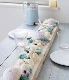 Les compositions en coquillages, bois flotté et coraux sont une valeur sûre de décoration de table qui fait rêver d'îles paradisiaques, de palmiers et de fleurs exotiques