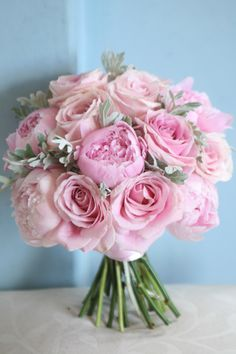 Pink wedding bouquet of peonies, roses and senecio foliage.