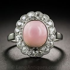 A gorgeous pink natural conch pearl is nestled in this classic Edwardian halo mounting finely handcrafted platinum over 14 karat white gold, and framed by 1.00 carat of sparkling old mine-cut diamonds. . Conch pearls are a very rare natural pearl from the Queen Conch and exhibit a characteristic flame structure on the surface of the gem. This gorgeous specimen is a very pretty, bright pink  'angel skin' color. Viennese hallmarks (a rare pedigree). Size 5.