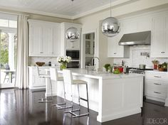 Pendant lights by Tom Dixon hang above the marble-top kitchen island, the cabinetry is custom made, the oven and stove are by Wolf, and the walls are painted in Benjamin Moore's Decorators White.   - ELLEDecor.com