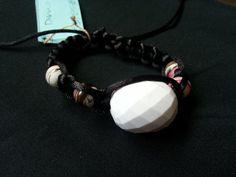 Pulseira feita em macramê com fio de seda preto, peça em resina branca e pequenas bolinhas rajadasTamanho ajustávelPeso: 20 gr