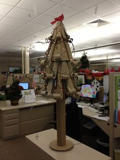 "I love reimagining things like this Christmas tree I made from recycled cardboard tubes in the ""decorate your cubicle contest"" at work. It's topped by a cardboard cut out red glitter cardinal, and surrounded by snowflakes cut out of white packing foam as well as silver pipe cleaners. Added a $10 string of delicate branch micro lights from Craft Warehouse, and finished by placing large red sequins as berries on the branches."