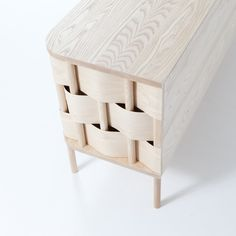 """Des barres en bois sont verticalement reliées au plateau. Elles sont à moitié """"enroulées"""" de manière alterné avec des bandes horizontales. Cela créer une surface forte solidifié (les forces s'exercent les unes contre les autres)"""