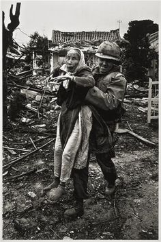 US Army chaplain evacuates an elderly Vietnamese woman, Tet Offensive, Hué, South Vietnam, February 1968