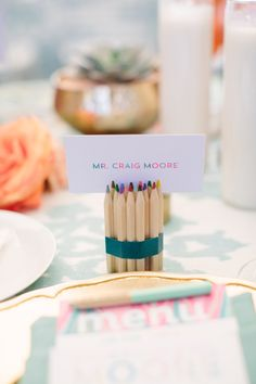 Colored pencils holding place cards. Amorology Weddings.