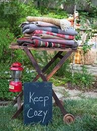 What a clever idea for an outdoor party... Cozy Blankets for the guests to use. On a rack or table, eclectic designs, warm fabrics!