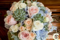 Soft pastel shades of blush pink and pale blue mixed with grey foliage and succulents