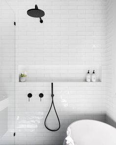 This minimalist bathroom, which uses only white subway tiles, shows off the versatility of the tile for use in all areas of the home. Bathroom Vinyl, Laundry In Bathroom, Bathroom Interior, Small Bathroom, Bathroom Ideas, Bathroom Niche, Shower Niche, Bathtub Shower, Bathroom Rugs