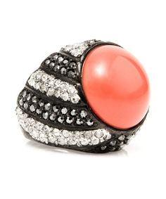 Turn heads with this epic coral top ring. The base of the gunmetal ring is designed with black and clear crystals in a creative pattern. The crystals come together at the top of the piece to encase the large coral stone. $125.00 by Max & Chloe